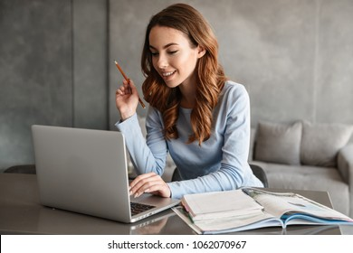 Portrait of a pretty young woman studying while sitting at the table with laptop computer and notebook at home
