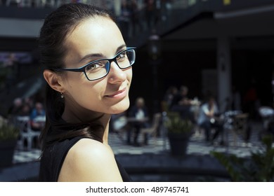 Portrait of pretty young woman stunning smile and cute looks closeup. Beautiful girl in casual clothes, dreaming, peacefully, outdoor, in cafe, in mall.