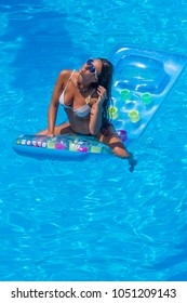 portrait of pretty young woman in swimsuit lying on a inflatable mattress at swimming pool.