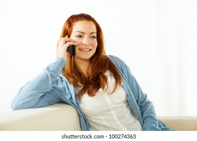 Portrait of a pretty young woman talking at mobile phone