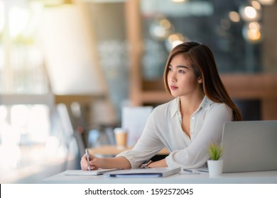 Portrait of pretty young woman using her laptop in the office.