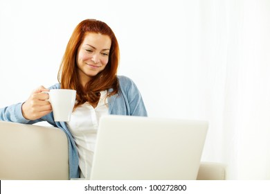 Portrait of a pretty young woman working relaxed on laptop