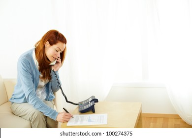 Portrait of a pretty young woman working and talking at phone