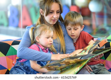 Portrait of pretty young women reading fairy tales with two children in the shopping center