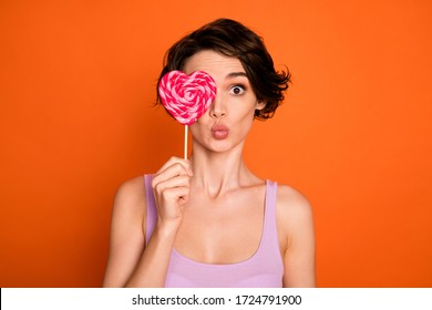 Portrait of pretty youth girl have summer free time hold lollipop close cover eye send air kiss wear stylish trendy singlet isolated over bright shine color background