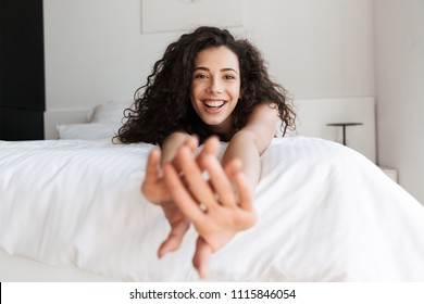 Portrait of prettyy european woman with long curly hair lying in bed with white linen in apartment and stretching arms to you with smile