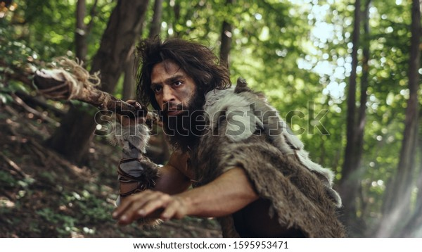 Portrait of Primeval Caveman Wearing Animal Skin and Fur Hunting with a Stone Tipped Spear in the Prehistoric Forest. Prehistoric Neanderthal Hunter Scavenging with Primitive Tools in the Jungle
