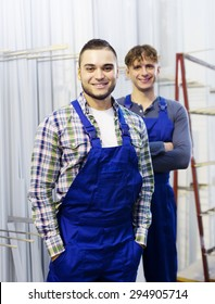 Portrait of production workers in coveralls with window profiles