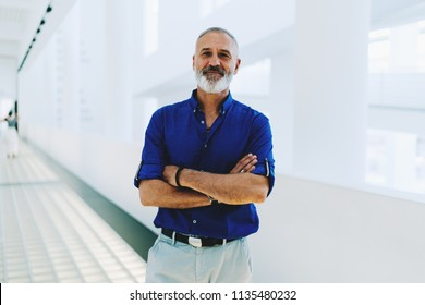 Portrait of a professional aged journalist with white beard wearing blue shirt and white trousers standing in the office corridor smiling at the camera with his hands crossed on the chest.