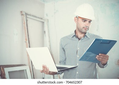 Portrait of professional architect working at the notebook in helmet with documents indoors