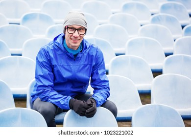 Portrait of professional athlete looking at camera sitting on stadium seat.