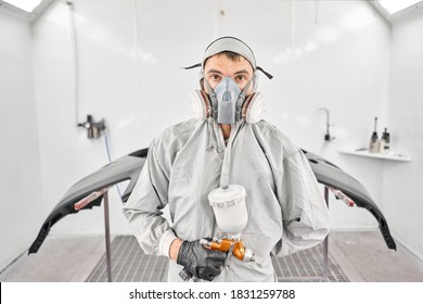 Portrait of professional auto painter. Worker painting parts of the car in special painting chamber, wearing costume and protective gear. Car service station.