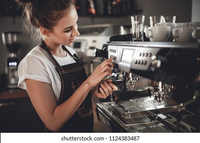 Portrait of professional barista woman in apron making coffee using machine at cafe