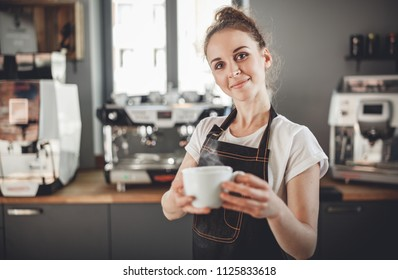 Portrait of professional barista woman in apron holding cup of hot coffee at cafe