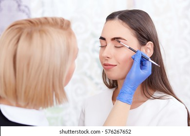 Portrait of professional blonde cosmetologist in blue gloves making permanent eyebrows for woman, using brush. Female client with closed eyes smiling and enjoying in beauty salon.