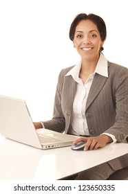 Portrait of a professional business woman at desk with laptop computer looking at camera isolated on white