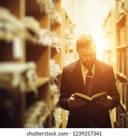 Portrait of professional businessman in library. Read the book