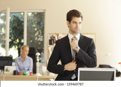 Portrait of a professional businessman sitting on office desk and adjusting his tie