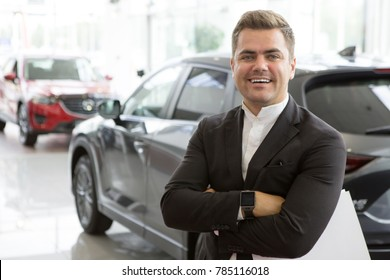 Portrait of a professional car salesman posing confidently at the dealership salon new cars on the background copyspace positivity friendly assistant worker manager retailer seller sales occupation.