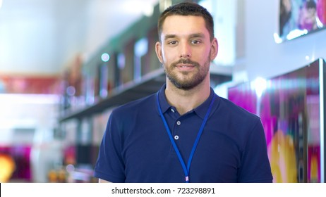 Portrait of a Professional Expert Consultant Smiles and Looks into Camera as Stands in the Bright, Modern Electronics Store Full of Latest Models of TV Sets, Cameras, Tablets and other Devices.