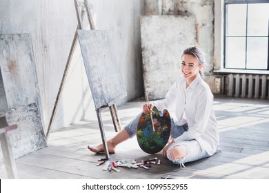 Portrait professional female artist painting on canvas in studio. Woman painter painting at workspace.