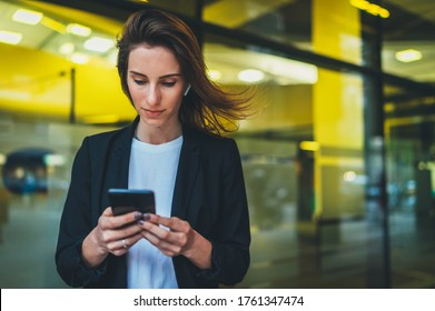 portrait professional female finance lawyer standing near office in evening street communicates online by cellphone. businesswoman pushing message on mobile phone on background yellow neon lights
