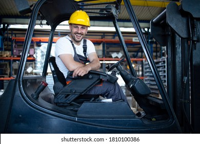 Portrait of professional forklift driver in factory's warehouse.