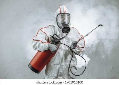 portrait of professional full armed disinfector against COVID 10, using sprays for removing bacterias from surface. wearing protective mask, gloves and suit. pandemic, epidemic, coronavirus concept