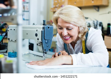Portrait of professional happy mature woman tailor working on sewing machine at studio