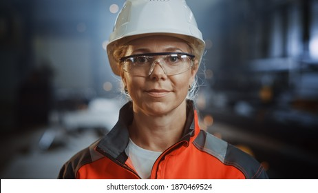 Portrait of a Professional Heavy Industry Engineer Worker Wearing Uniform, Glasses and Hard Hat in a Steel Factory. Beautiful Female Industrial Specialist Standing in Metal Construction Facility.