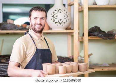 Portrait of Professional Male Ceramist Holding Wooden Tray with Clay Handmade Cups. Posing in Protective Apron in Workshop.Horizontal Shot