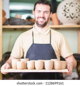 Portrait of Professional Male Ceramist Holding Wooden Tray with Clay Handmade Cups. Posing in Protective Apron in Workshop. Focus on Cups.Square Image