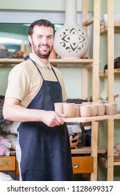 Portrait of Professional Male Ceramist Holding Tray with Clay Handmade Cups. Posing in Protective Apron in Workshop. Vertical Image Composition