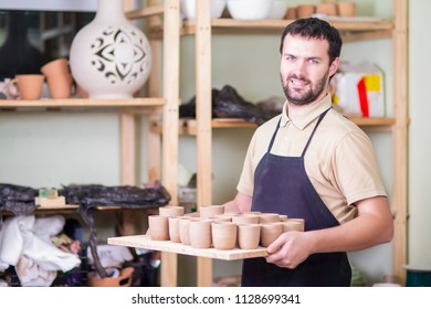 Portrait of Professional Male Ceramist Holding Tray with Clay Handmade Cups. Posing in Protective Apron in Workshop.Horizontal Image Composition