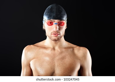 Portrait of a professional man swimmer over black bakground.