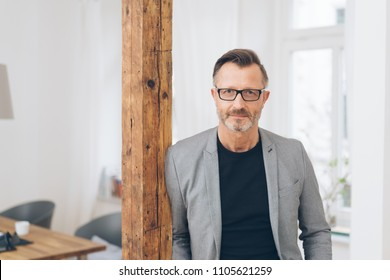 A portrait of professional, mature man leaning against a timber pillar in a private, home setting.