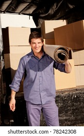A portrait of a professional mover with a carpet and boxes in the background