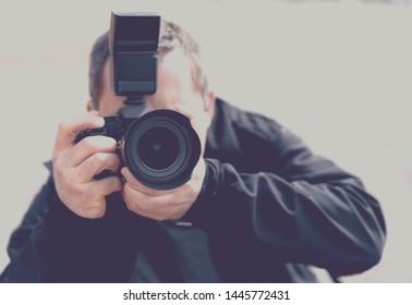 Portrait of a professional photographer with a camera pointed toward the subject