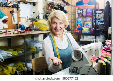 Portrait of professional positive elderly female tailor working on sewing machine at studio