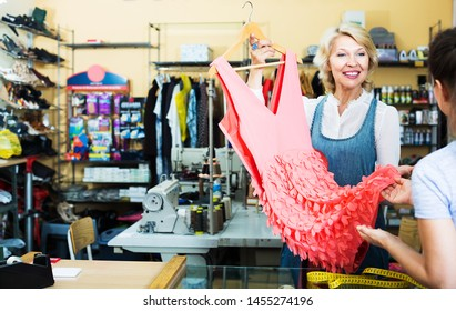 Portrait of professional positive mature female tailor showing dress to customer at counter in sewing atelier