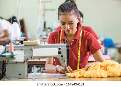 portrait of professional Seamstress in textile factory sewing with industrial sewing machine at garment