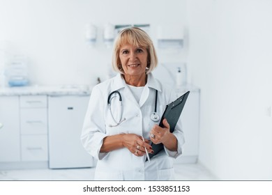 Portrait of professional senior doctor in clinic with notepad in hands.