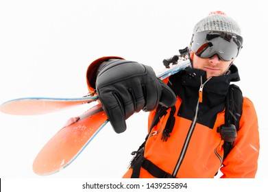 Portrait of a professional skier athlete in a knitted hat and orange-black suit with a black ski mask with skis on his shoulder during a snowstorm on a light background in the snow. Wide angle