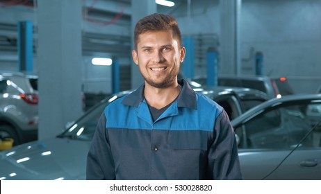 Portrait of Professional smiling car mechanic working in modern auto repair service