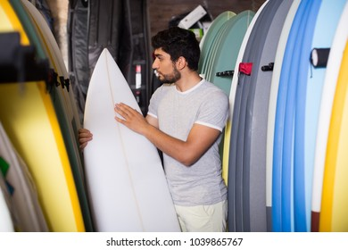 portrait of professional surfer with board for surfing in the shop