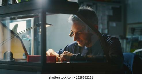 Portrait of a professional watchmaker repairer working on a luxury mechanism watch gears in a workshop.