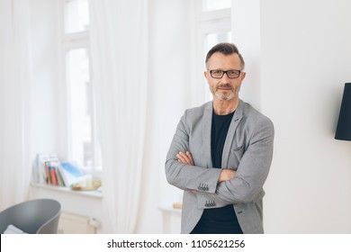 A portrait of a professional, well dressed, mature man with arms folded in a private, home scene.