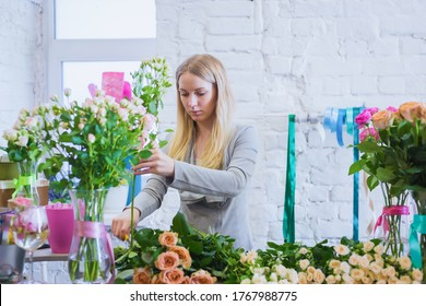 Portrait of professional woman floral artist, florist cutting flowers on table against white brick wall at flower shop, workshop, studio. Floristry, handmade, preparation and small business concept