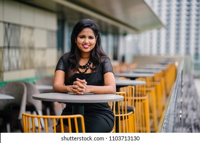 Portrait of a professional young Indian woman sitting at a table with a city view in the background. She is smiling confidently and enjoying the warm weather.