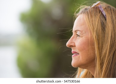 Portrait profile attractive mature woman with thoughtful facial expression sitting lonely outdoor, blurred background, copy space.